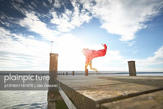 Mädchen läuft über einen Steg, Starnberger See, Oberbayern, Bayern, Deutschland - p1316m1161070 von Jan Greune