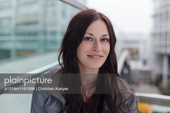 Junge Frau lächelt in die Kamera, München, Bayern, Deutschland - p1316m1161098 von Christian Kasper