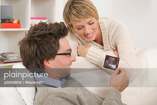 Couple, Man looking at ultrasound photos - p3006804f by Westend61