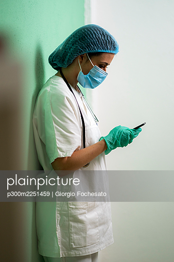 Female doctor using mobile phone while standing against wall at clinic - p300m2251459 by Giorgio Fochesato