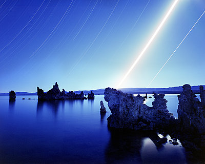 Scenic view of Tufa in Mono Lake against star trails at night - p1166m1526600 by Cavan Images