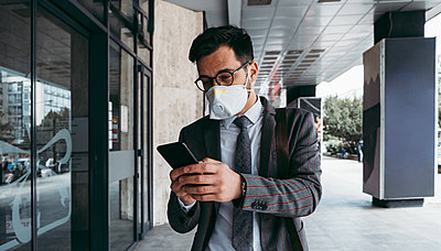 Business man with protective face mask using phone on city street. - p1166m2179399 by Cavan Images