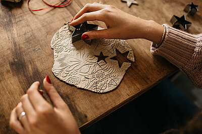 hands of young woman sitting at table creating ornaments with clay - p1166m2235310 by Cavan Images