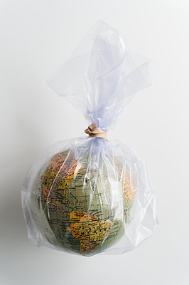 Earth globe in plastic bag - p1427m2186303 by Jamie Grill