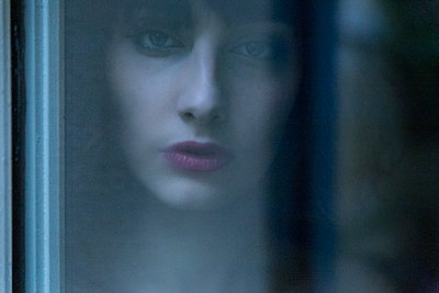 Young woman looking through a window during winter - p1619m2191650 by Laurent MOULAGER