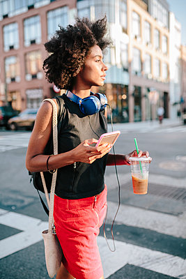 Young woman with headphones and smart phone crossong street in Brooklyn, carying take away drink - p300m1417126 by Giorgio Fochesato
