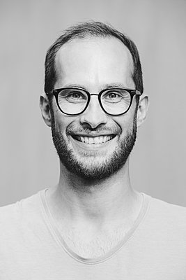 Portrait of smiling man wearing glasses - p300m2023938 by Nadine Ginzel