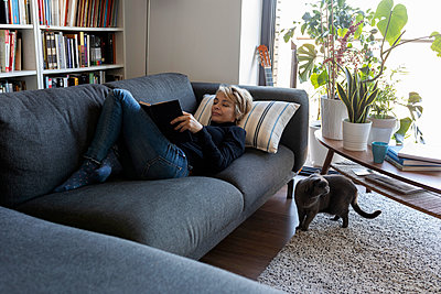 Mature woman relaxing on couch at home reading a book - p300m2144940 by Valentina Barreto
