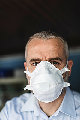 Mature man with protective mask looking at camera - p300m2180468 by 27exp
