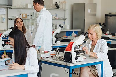 Senior female researcher in a white coat working in lab surrounded by other researchers - p300m2250197 by Hernandez and Sorokina