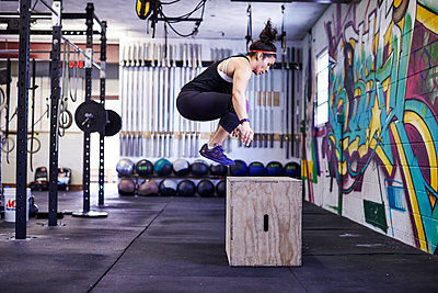 A female athlete trains in a crossfit gym.  - p343m1184157 by Josh Campbell
