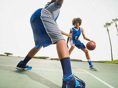 Teenage boys playing basketball on court - p555m1415519 by Erik Isakson