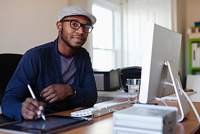 Black designer working at desk - p555m1479736 by Roberto Westbrook