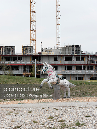 Wooden rocking horse with graffiti in front of a construction site - p1383m2116834 by Wolfgang Steiner
