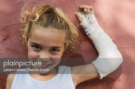 Portrait of smiling blond girl with plastered arm - p300m1189463 by Ramon Espelt