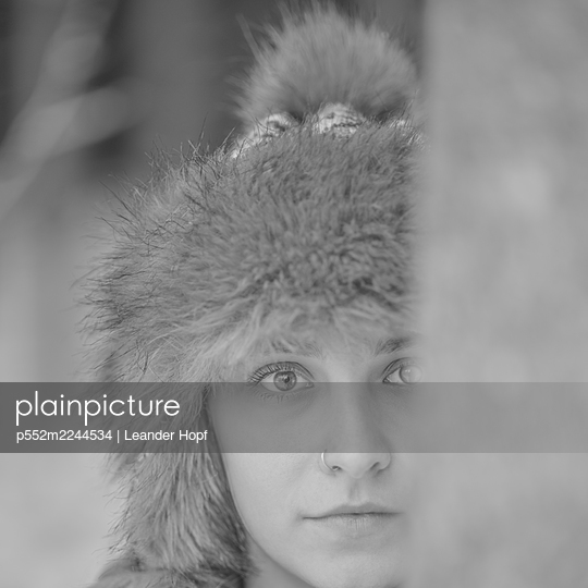Young woman with nose piercing and fur hat - p552m2244534 by Leander Hopf