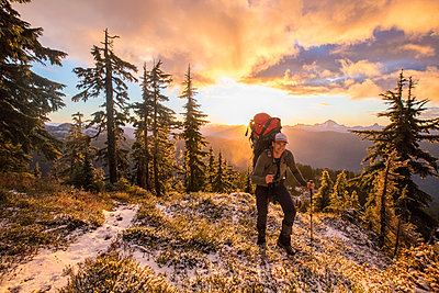 Front view of backpacker hiking over scenic mountain ridge at sunset - p1166m2255902 by Cavan Images