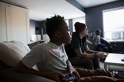 Boy playing video game in living room - p1192m1567257 by Hero Images