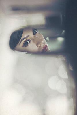 Gesicht einer jungen Frau im Rückspiegel eines Autos - p1248m1185555 von miguel sobreira