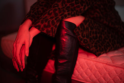 Young woman in leopard print faux fur coat and boots - p1321m2181597 by Gordon Spooner