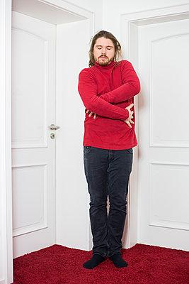 Man in red sweater hugs himself, portrait - p1621m2231957 by Anke Doerschlen