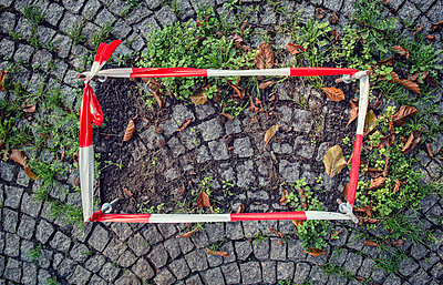 Germany, fixed barrier tape arround damaged cobblestone pavement - p300m983547f by Ophelia photography