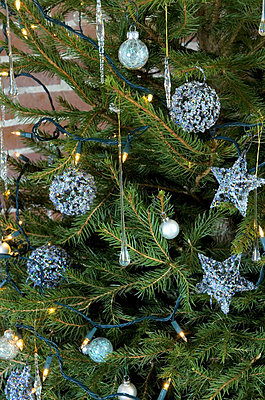 Metallic light blue baubles and fairylights on Christmas tree in rural Suffolk home - p349m790975 by Polly Eltes
