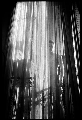 Man stands behind translucent curtain - p3720274 by James Godman