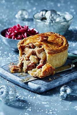 Turkey pie on cutting board, seasonal Christmas food - p429m2068554 by Danielle Wood