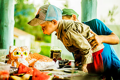 Caucasian boy blowing out candles on birthday cake - p555m1412351 by Aleksander Rubtsov