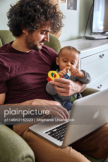 Father with laptop and baby boy, Stay at home due to Covid-19 - p1146m2182023 by Stephanie Uhlenbrock