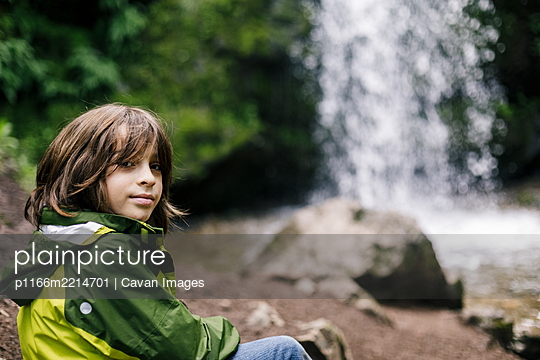 Smiling child sitting on rock by waterfall in regional park - p1166m2214701 by Cavan Images