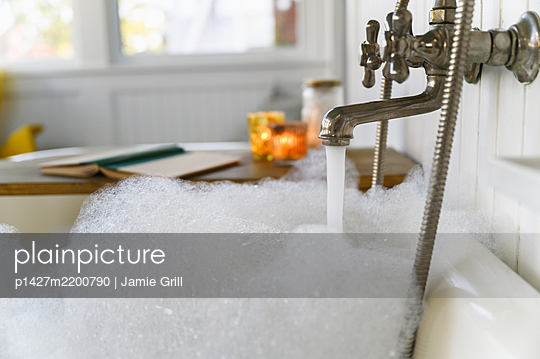 Bubble bath with book and candles - p1427m2200790 by Jamie Grill