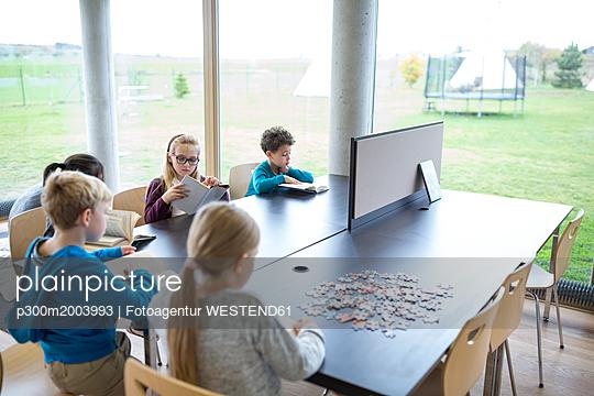 Pupils reading books on table in school break room - p300m2003993 von Fotoagentur WESTEND61