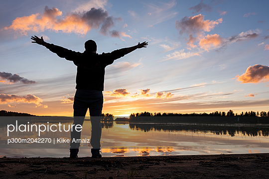 Finland, Kajaani, Man watching sunset at the river with arms outstretched - p300m2042270 von Kike Arnaiz
