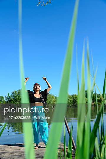 Woman with headphones dancing on the lakefront - p427m2203625 by Ralf Mohr