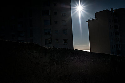 Sun shining in the sky between two dark buildings - p1007m1134126 by Tilby Vattard