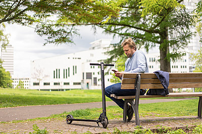 Businessman with E-Scooter sitting on bench in city park using smartphone, Essen, Germany - p300m2114549 by Joseffson