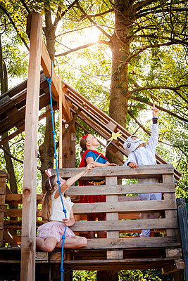 Three kids with superheroes costumes playing on their tree house - p300m2140034 von Epiximages
