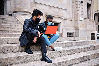 Friends wearing protective face mask using laptop while sitting on steps in city - p300m2250237 by Alvaro Gonzalez