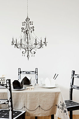 Personalised chairs at table under ornate glass chandelier - p349m695257 by Jon Day