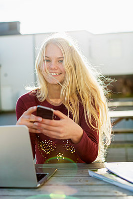 Portrait of happy teenage girl with mobile phone and laptop at table outdoors - p426m920103f by Kentaroo Tryman