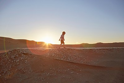 Boy walking on sand dune, Namib Naukluft National Park, Namib Desert, Sossusvlei, Dead Vlei, Africa - p429m1029857 by Stephen Lux