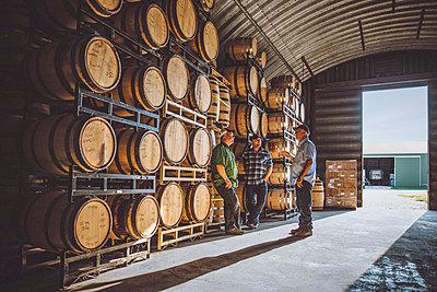 Caucasian men talking near barrels in distillery - p555m1522988 by John Fedele