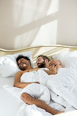 Gay couple sleeping in bedroom - p787m2115288 by Forster-Martin