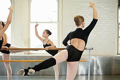 Ballerinas exercising at bar - p9245540f by Image Source