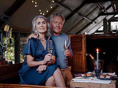 Portrait of senior couple having a candlelight dinner on a boat in boathouse - p300m2156232 von Gustafsson