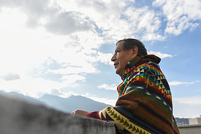 Thoughtful man wearing poncho looking away at rooftop - p300m2290479 by MORNINGVIEW AGENCY