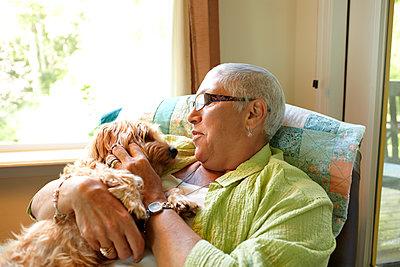 Caucasian woman holding dog - p555m1479203 by Granger Wootz