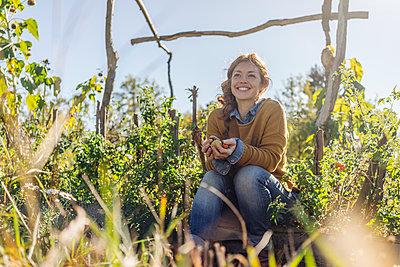 Junge Frau entspannt sich im Schrebergarten - p586m1214260 von Kniel Synnatzschke